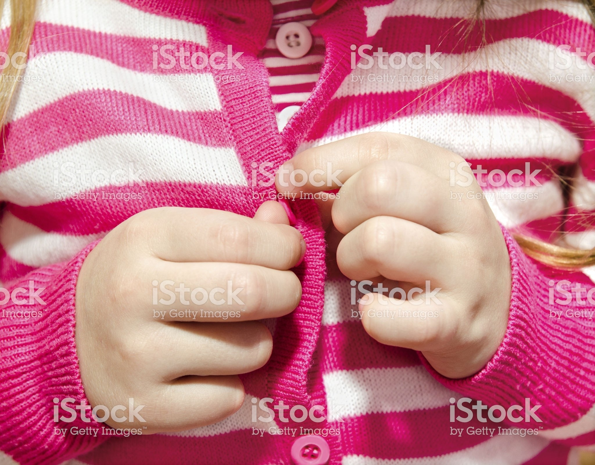 Little girl buttoning her jacket closeup